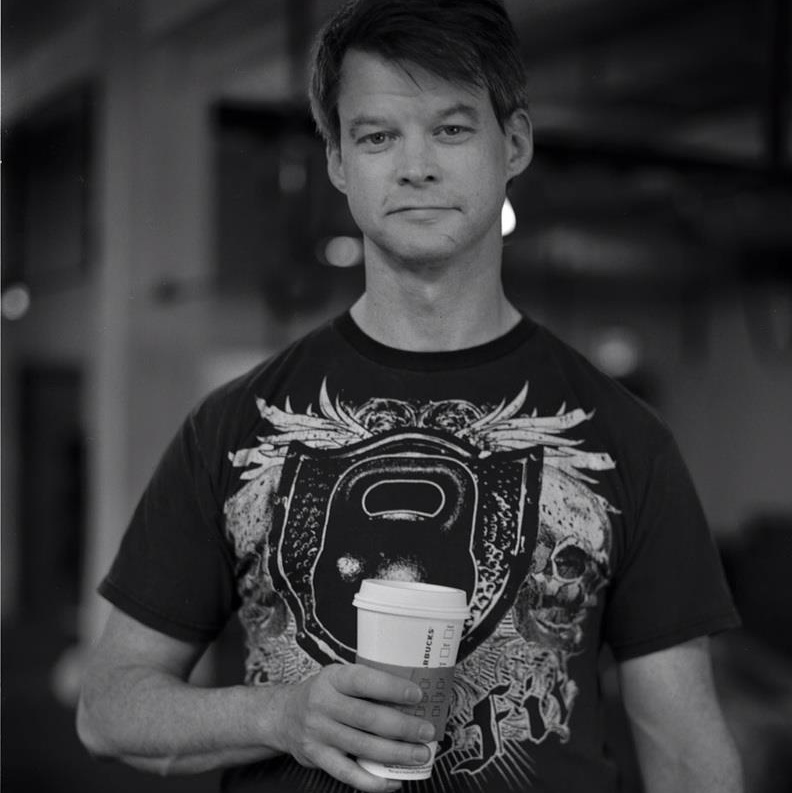 black and white photo of a white man holding a takeaway coffee cup