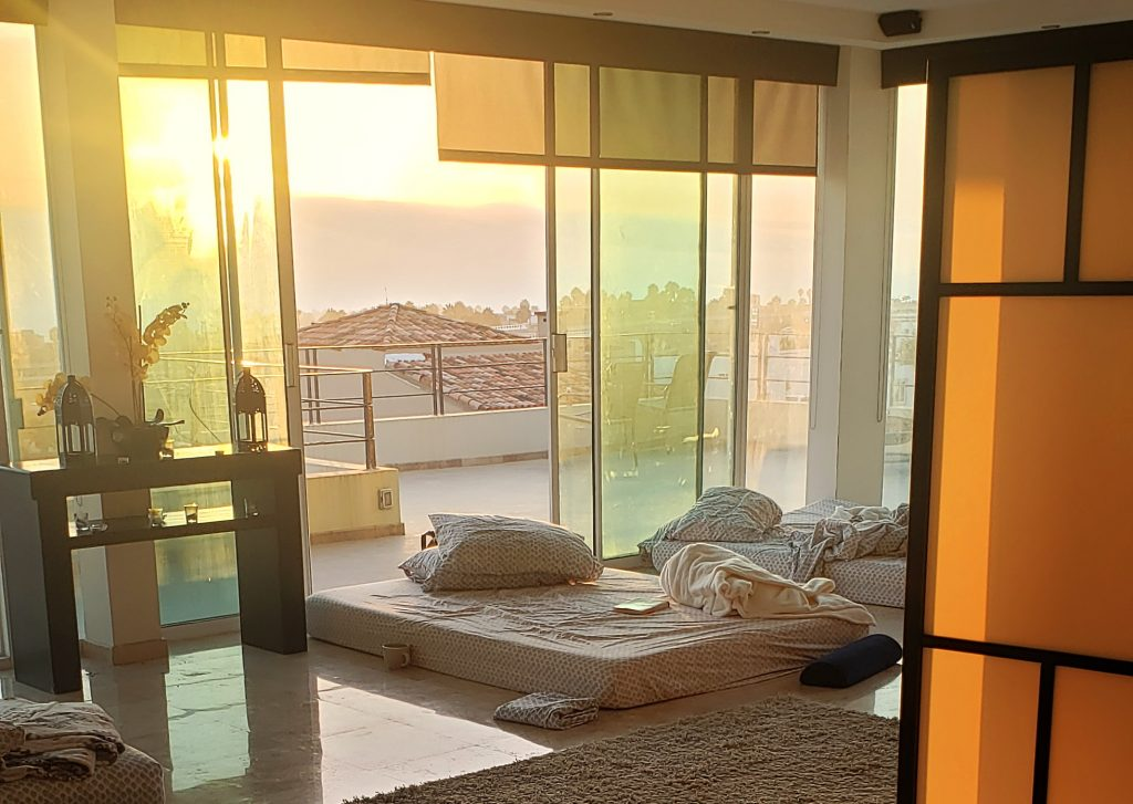 Photo of a mattress on the floor, near big glass windows where the sun is rising where the ibogaine session took place