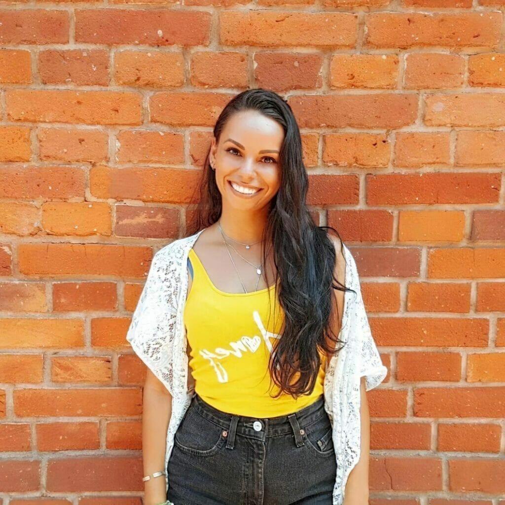 jessika-lagarde-headshot-photo-of-brazilian-woman-smiling-in-front-of-brick-wall