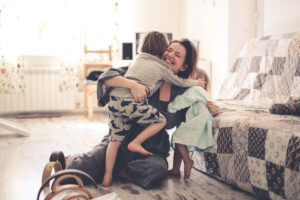 photo of a happy mom hugging her two toddler children on the floor and smiling to represent microdosing moms
